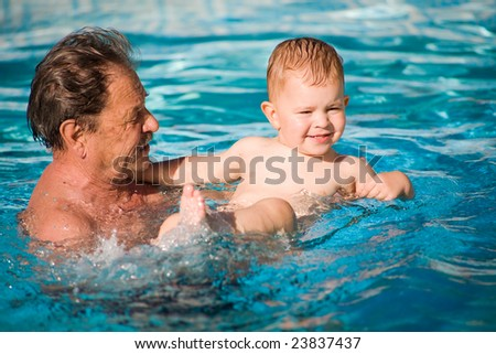 Grandfather and grandson swimming together in the pool. Outdoor, summer.