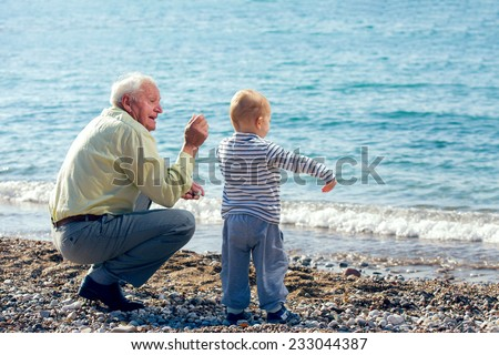 Grandfather and grandson throwing stones into the sea