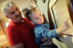 Grandfather and his grandson using touch screen in the museum