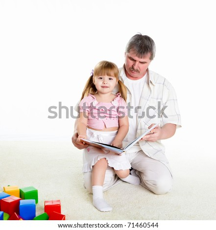 grandfather and his little granddaughter together reading a book