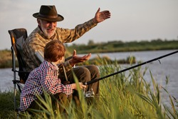 Grandfather and kid boy together fishing in the evening at sunset time in summer day on river in countryside, side view on caucasian multi-generation family, elderly man teach child boy to fish