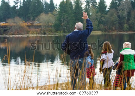 Grandfather and kids waving at a passing train on a lake.