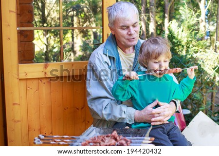 Grandfather and little boy making barbecue and eating grilled meat, outdoors.
