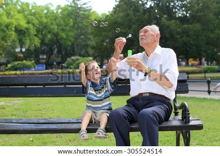 grandfather blowing soap bubbles to grandchild