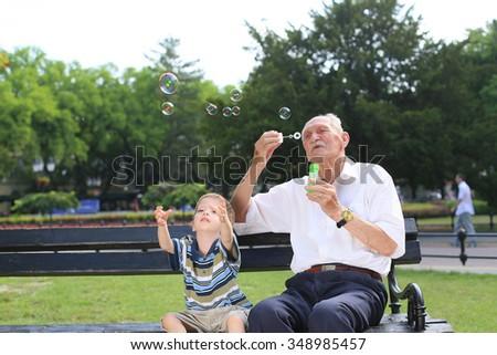 grandfather blowing soap bubbles to grandchild