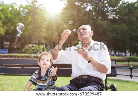 grandfather blowing soap bubbles to his grandchild stock photo
