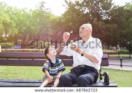 grandfather blowing soap bubbles to his grandchild #687862723