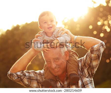 Grandfather carrying grandson on shoulders in park