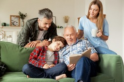 Grandfather enjoying literature together grandson and his young parents at cozy living room. Elderly man reading book aloud to cute schoolboy and his smiling family. Multi-generational family weekend