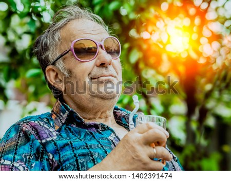 grandfather enjoys life with a glass of drink in his hand #1402391474