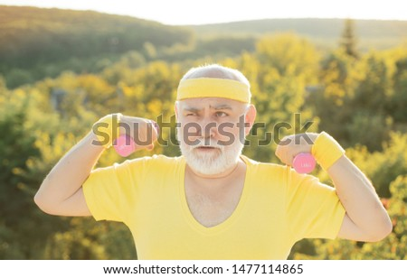 Grandfather exercising with dumbbell. Sport for senior man. Senior man in park working out with weights