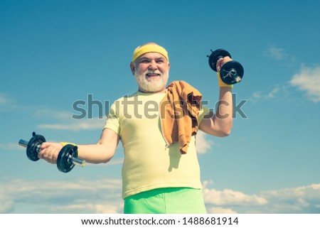 Grandfather exercising with dumbbell. Sport for senior man. Senior man lifting weights