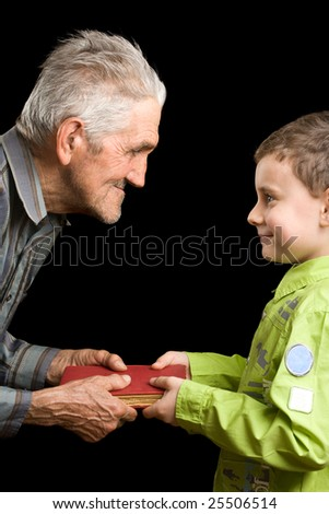 Grandfather giving a book to his grandson