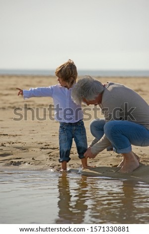 Grandfather helping grandson roll up pants at beach