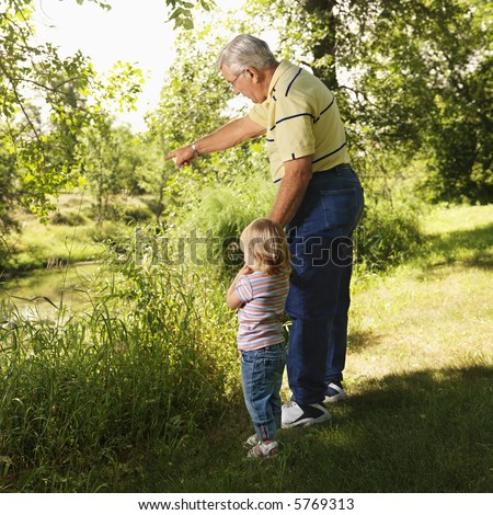 Grandfather holding granddaughter's hand by creek and pointing. - stock photo