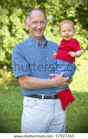 Grandfather holding happy grandson in sunny garden