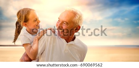 Grandfather holding his grandchild on his back against serene beach landscape #690069562