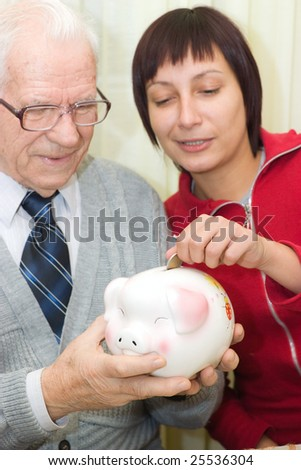 Grandfather holding piggybank while Granddaughter putting a coin - stock photo