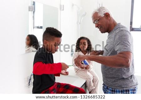 Grandfather In Bathroom Wearing Pajamas Helping Grandchildren To Brush Teeth