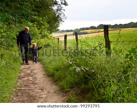 grandfather is walking with grandchild on a walking track