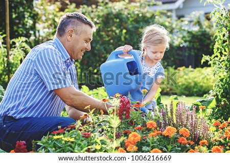 Grandfather is watering flowers with his granddaughter.