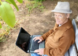 Grandfather on a bench with a laptop. Old age and modern electronics. Photo of mature man in eyeglasses using laptop while sitting on bench in green park