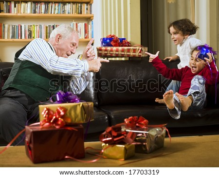 grandfather playing with grandchildren with presents