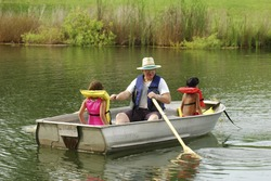 Grandfather rowing two kids in a boat.