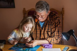Grandfather shows coins to a small beautiful granddaughter through a magnifier. The concept of common interests and family unity. Family values.