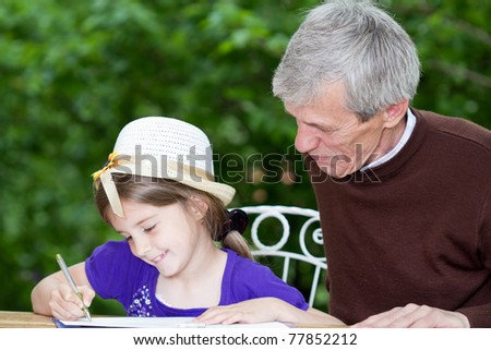 Grandfather spending time with little girl outside-little girl learning to write