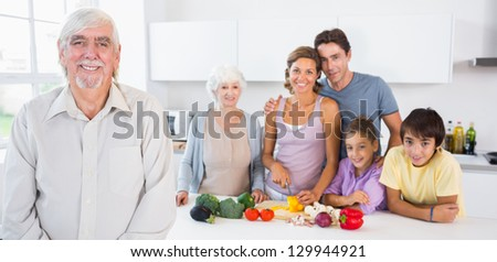 Grandfather standing by kitchen counter with family behind him