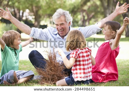 Grandfather Teaching Grandchildren To Build Camp Fire