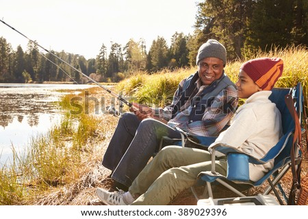 Grandfather Teaching Grandson To Fish By Lake