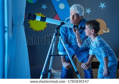 Grandfather teaching grandson using telescope to see the constellations and moon. Child seeing satellite using telescope with senior man. Granddad and grandchild using telescope to see moon surface.