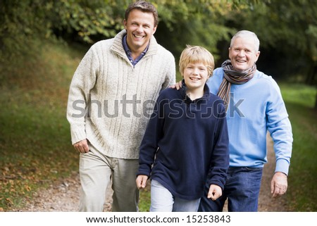 Grandfather walking with son and grandson along autumn path