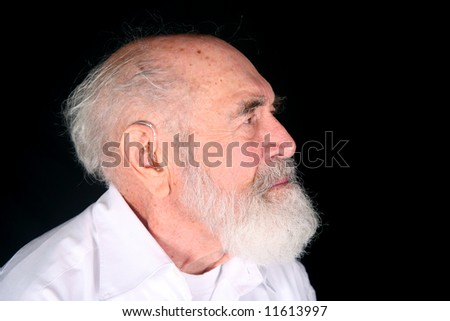 Grandfather wearing a custom hearing aid isolated on black background