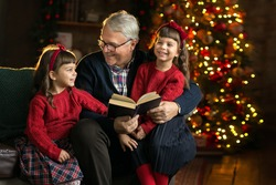Grandfather wearing glasses, reading a book to small granddaughters twins in a room decorated for Christmas on the background of a Christmas tree. Christmas holiday concept. contrast photography