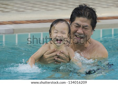 Grandfather with granddaughter in the pool at my home.