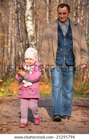 Grandfather with  granddaughter walk on wooden fllooring in wood in autumn