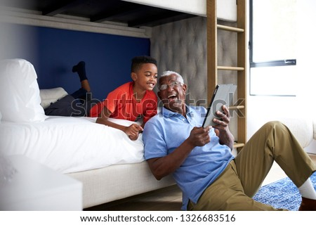 Grandfather With Grandson Lying In Bedroom Playing Game On Digital Tablet Together
