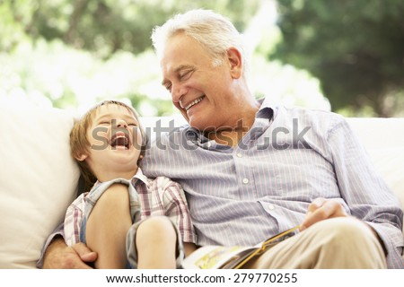 Grandfather With Grandson Reading Together On Sofa Stock photo ©