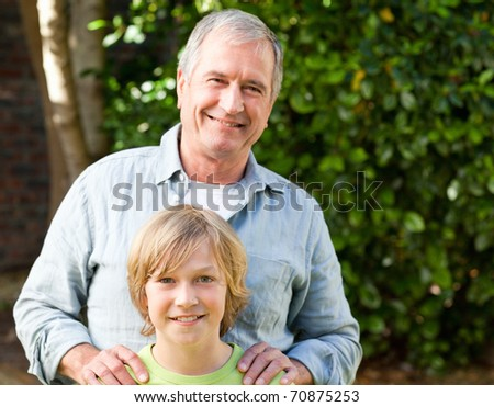 Grandfather with his grandson looking at the camera in the garden