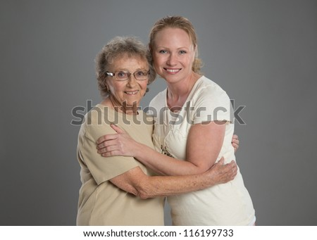 Grandma and Grand Daughter Hug Each Other on Grey Background
