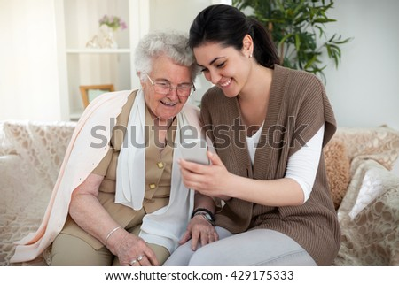 Grandma and granddaughter taking a picture over a smartphone