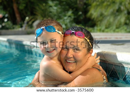 Grandma and her little treasure exercising the swimming pool with matching diving goggles