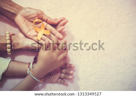 Grandma hand and grandson cancer awareness ribbon sign top view with vintage picture style.