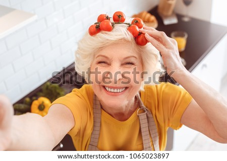 Grandma making selfie, smile, holding branch of tomatoes on head