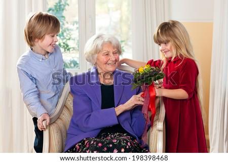 Grandma Receiving Flowers from Grandchildren looking very happy.