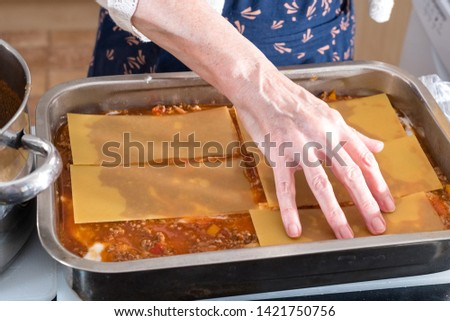 Grandma's Home Made Lasagne being Prepared in the Kitchen preparing the layered ingredients pasta, meat, sauce and a Topping of Cheese then ready for the Oven.