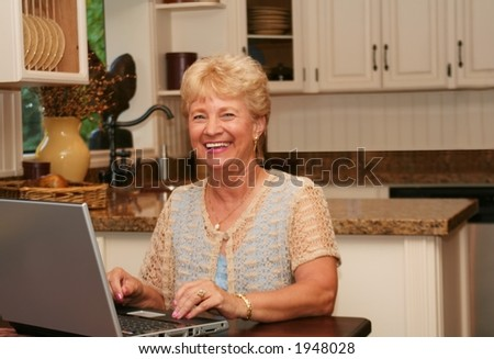 Grandma using her laptop in the kitchen.